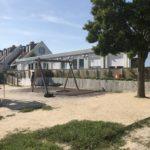 Verspiegelte Sonnenschutzfolie am Kindergartencontainer mit einem Spielplatz davor