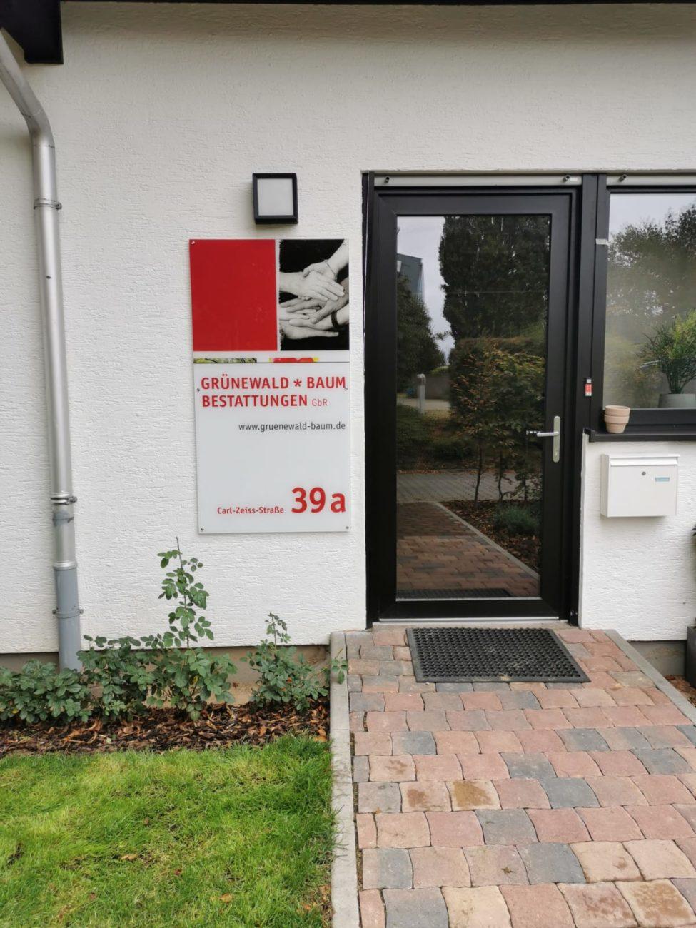 Firmenschild neben einer Haustür