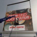 Montage eines Fassadenbanners aus Gitternetzplane für Möbel Martin